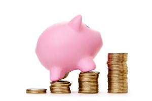 piggy bank climbing coin stacks